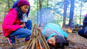 Campers building a camp fire.