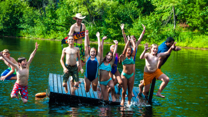 Campers jumping off a dock into the water.