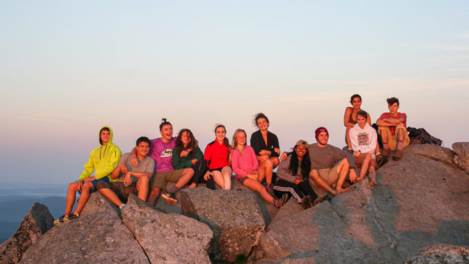 Campers sitting in a group at the top of the mountain.