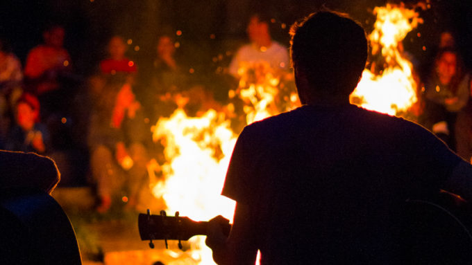 A camper playing the guitar at the camp fire.