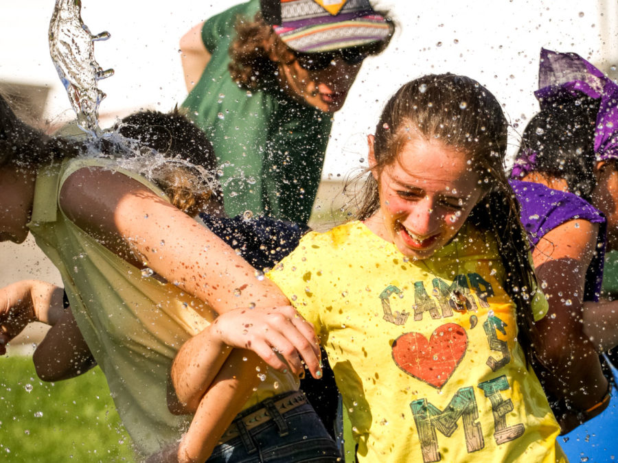 A camper getting water splashed on her while laughing.