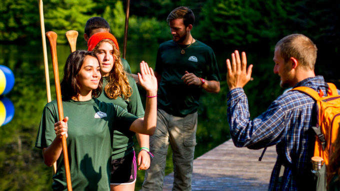 Campers high fiving each other on the dock.