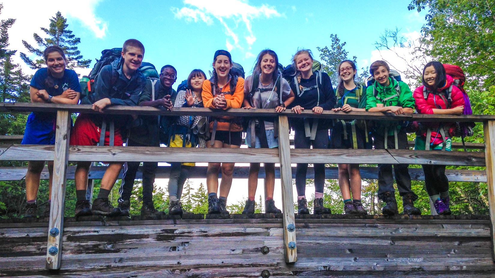 Campers on a bridge smiling at the camera