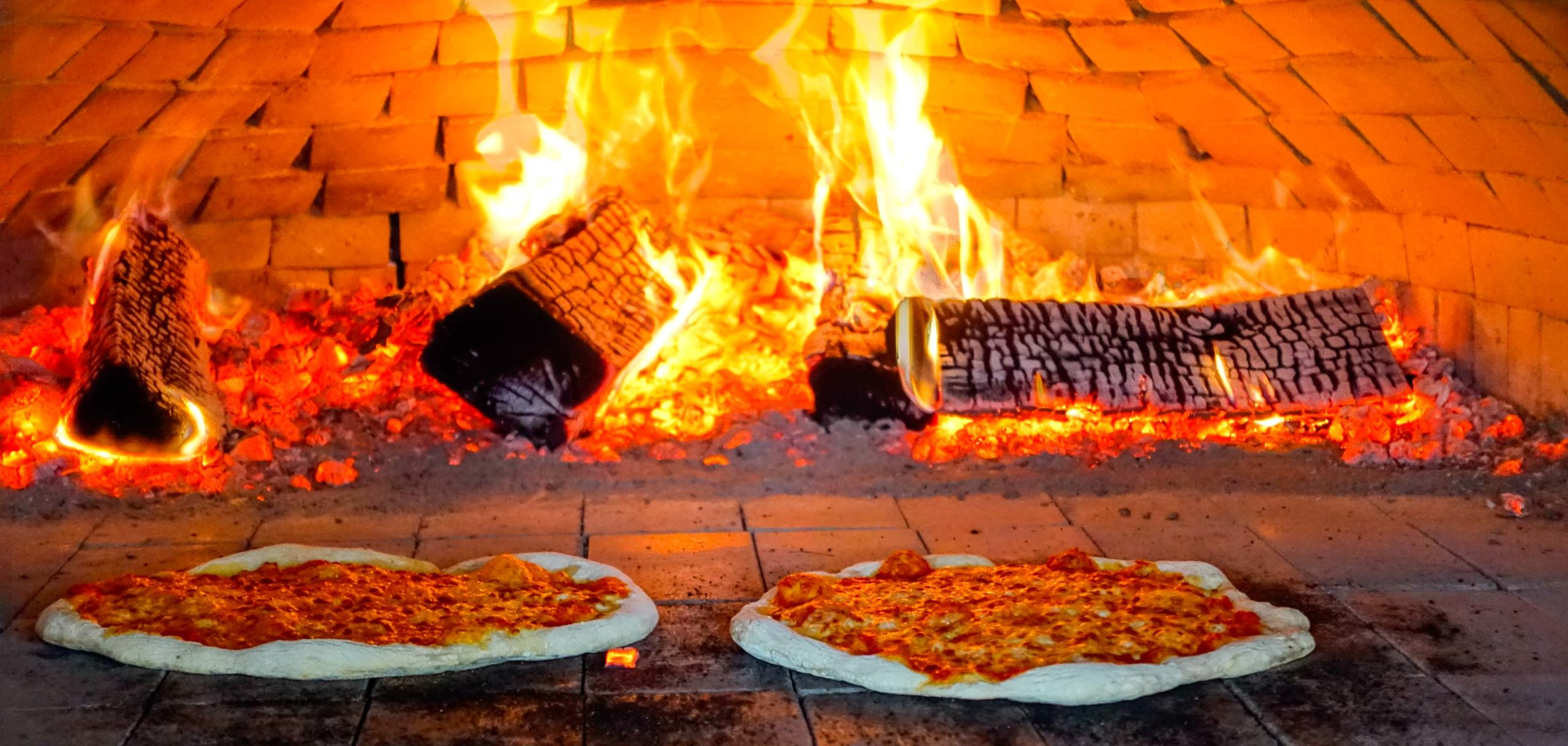 Pizzas being fired in a wood burning stove.