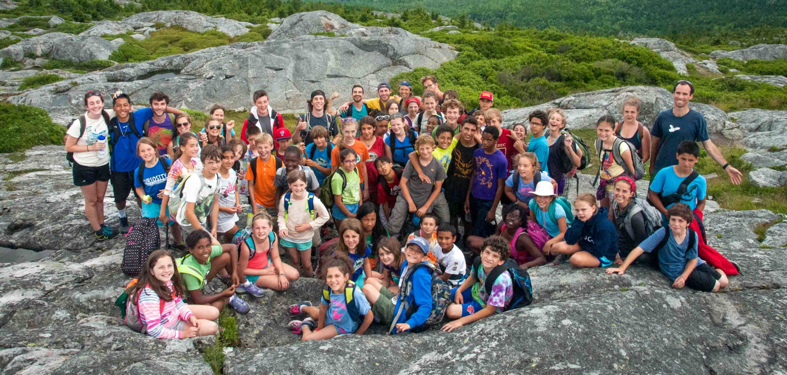 A large group of campers smiling at the camera on a hike on top of a mountain.