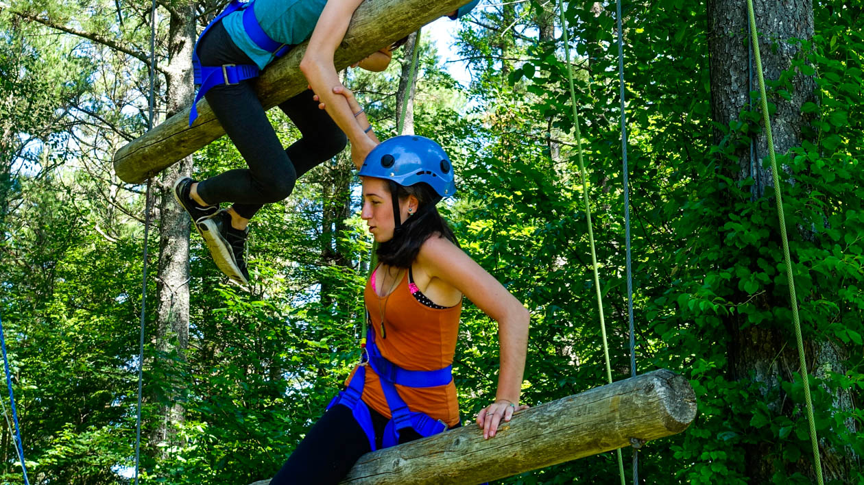Campers climbing on the high ropes course.