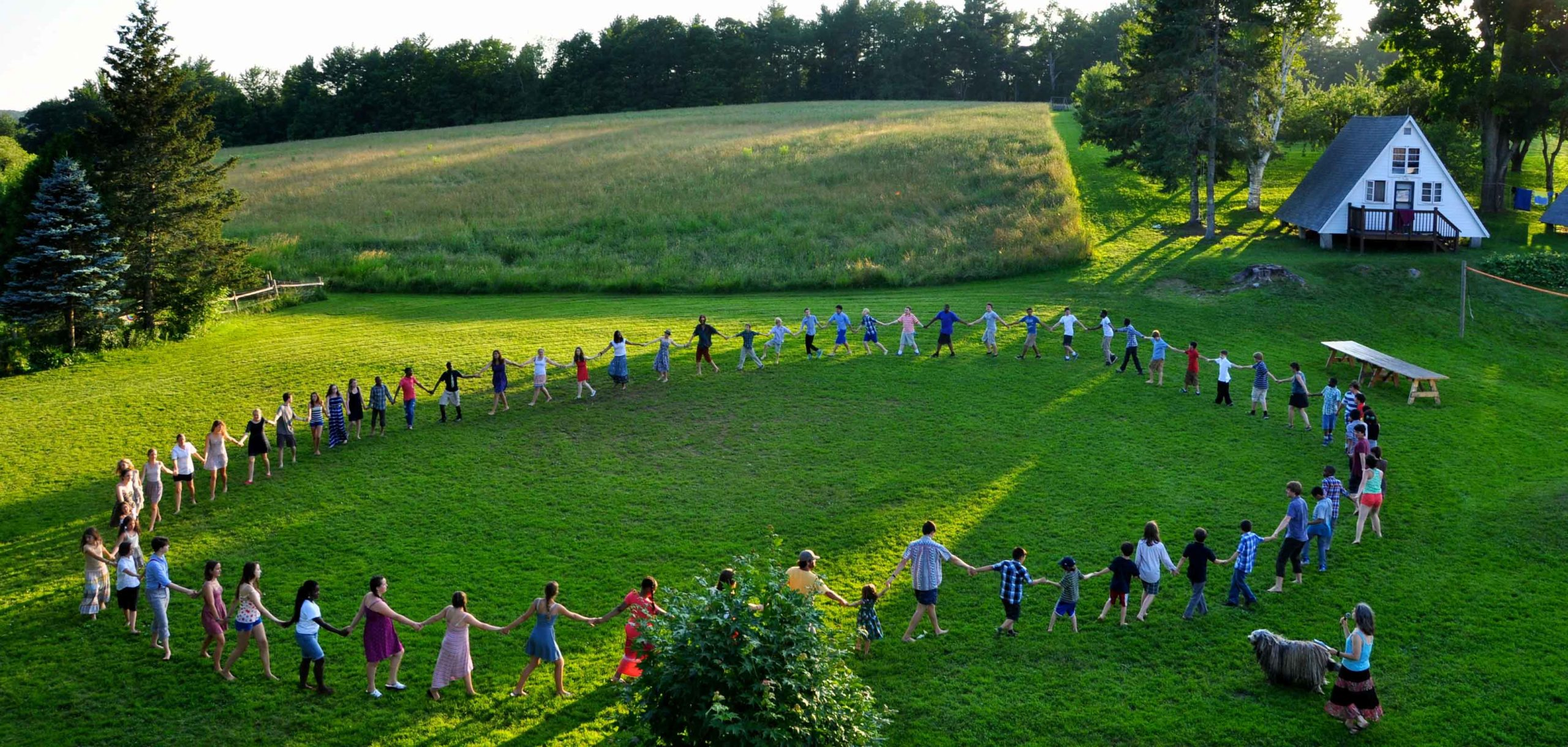 A view of people standing in a circle holding hands in a green field