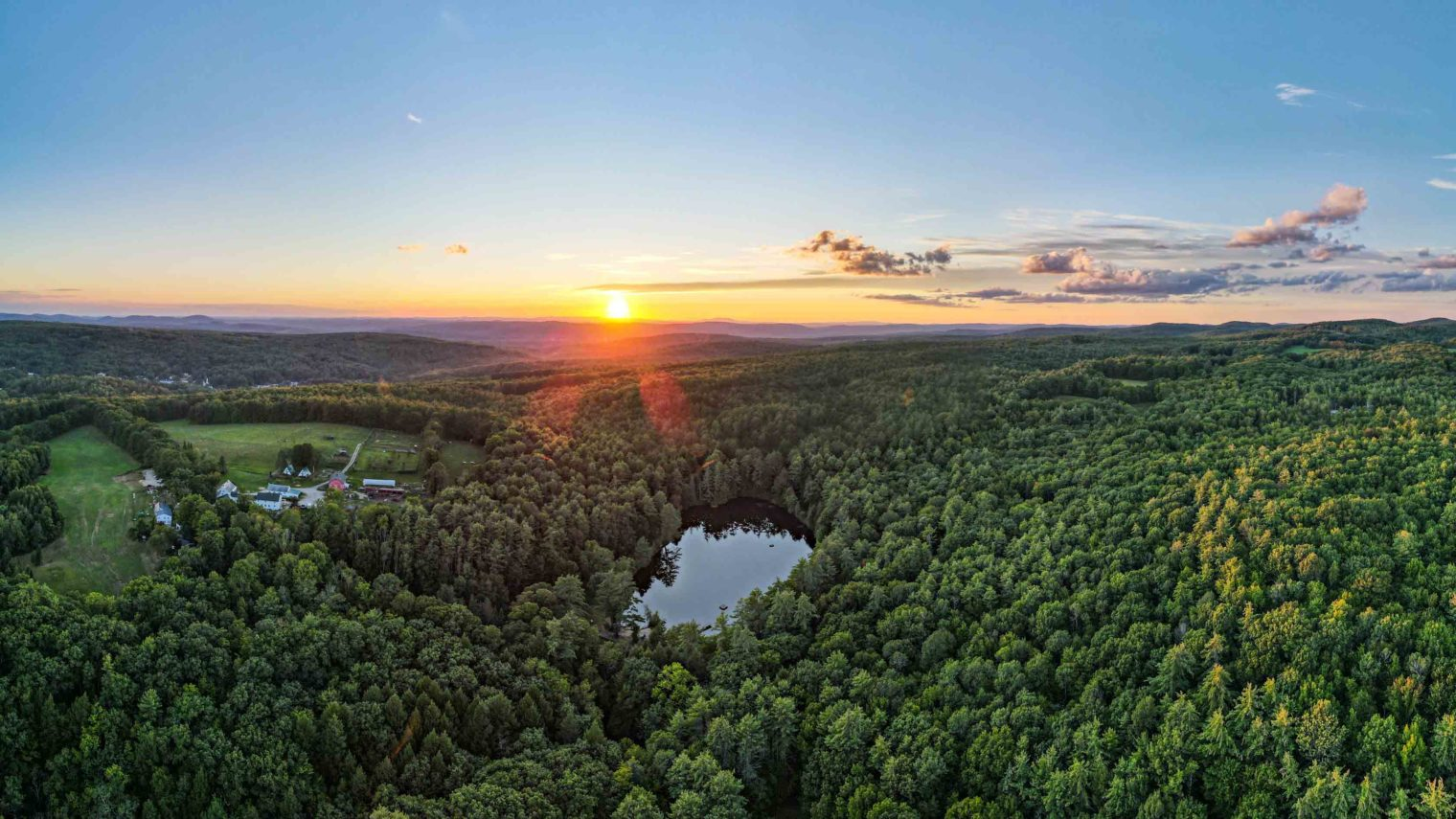 A sunset over the camp grounds and forest.
