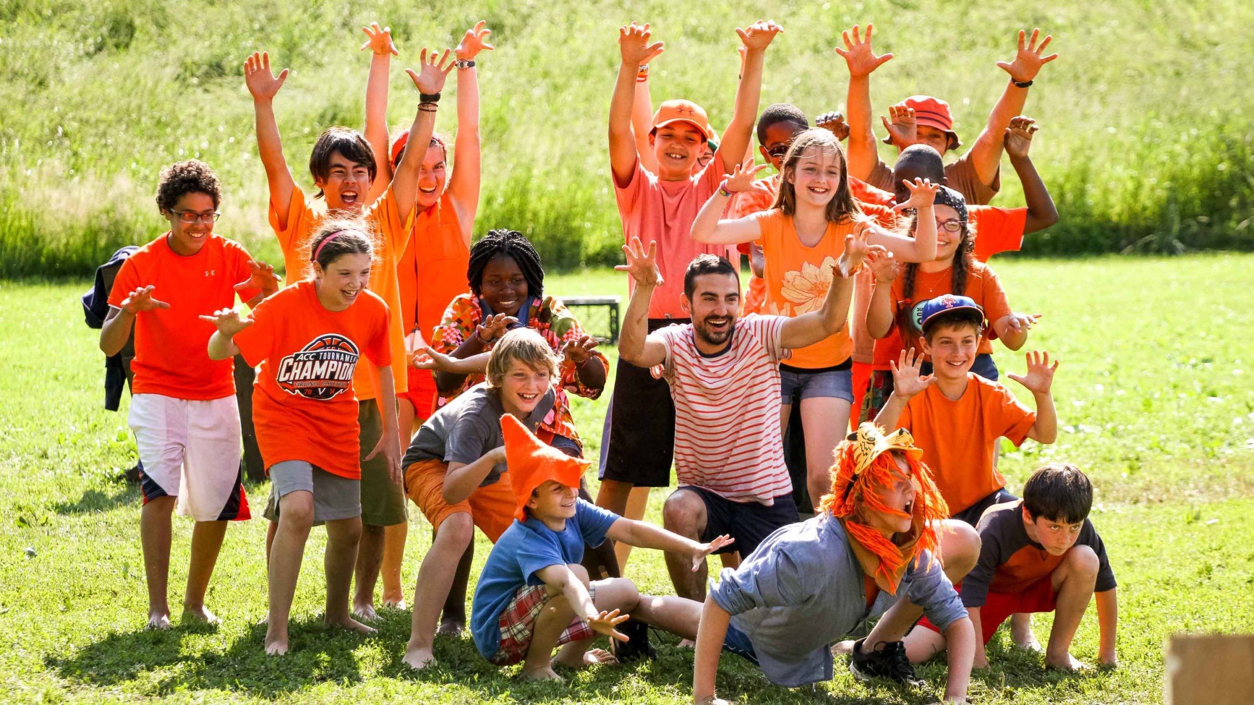 A group of campers posing wearing orange with their hands up.