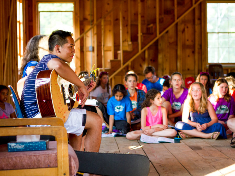 Campers listening to a musical performance.