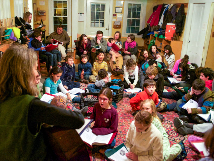 A group of campers sitting inside and singing together.