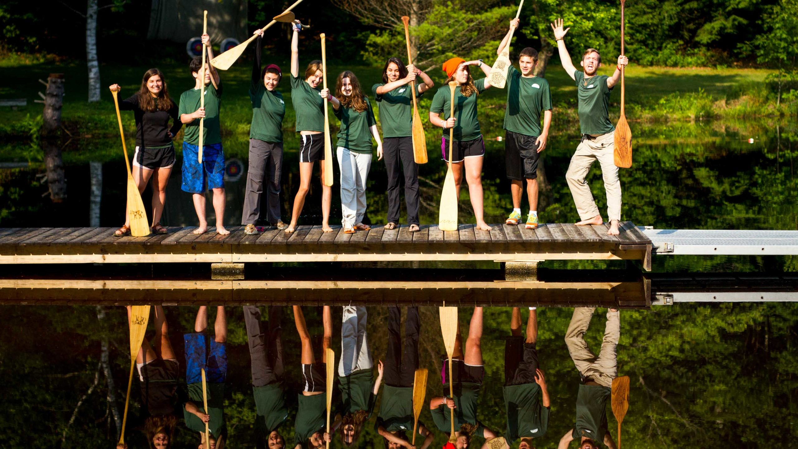 Campers standing on the dock holding paddles in the air.