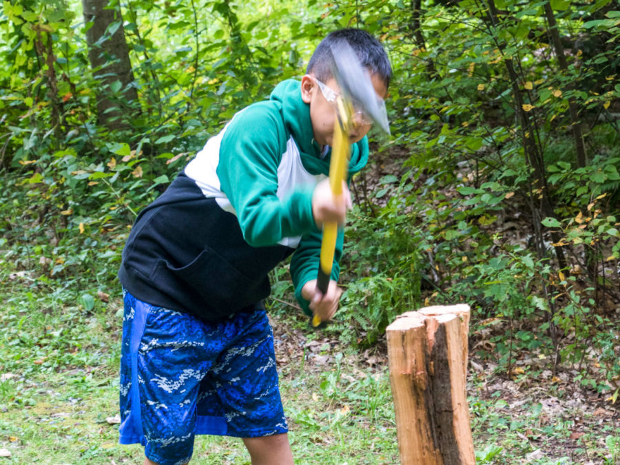 A camper learning how to chop wood