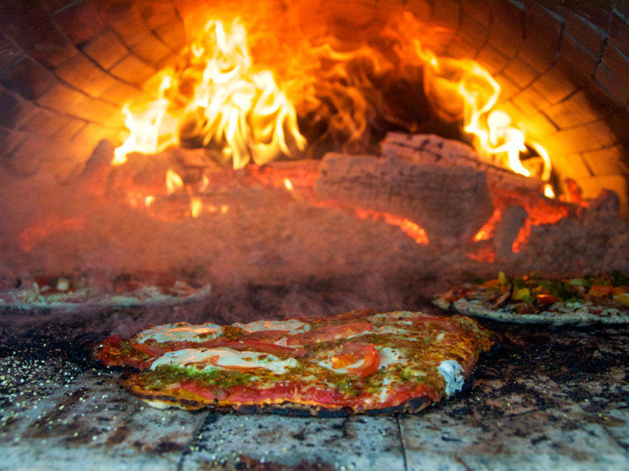 Pizza being baked in a wood oven.