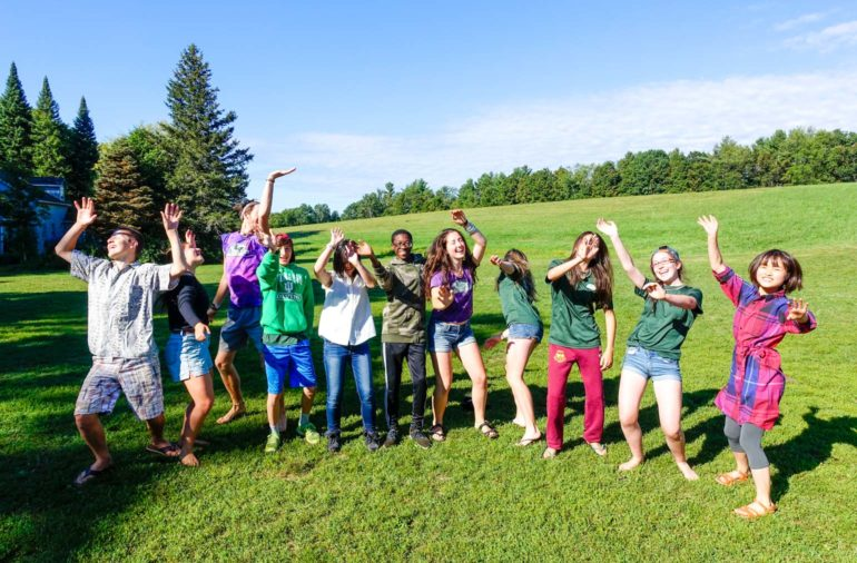 Campers dancing and posing for the camera in a green field.