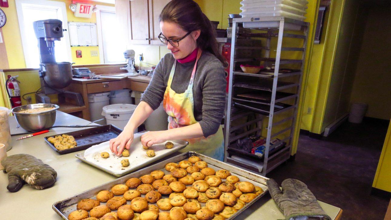 A staff member preparing cookies