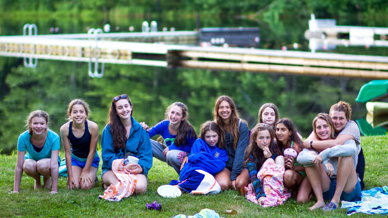 A group of campers sitting in front of the lake smiling.