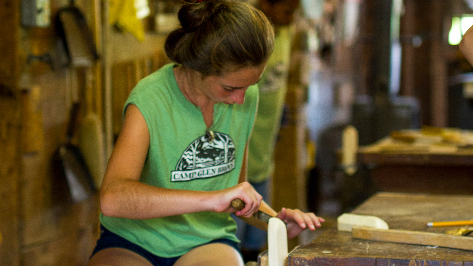 A camper working on a piece of wood in the woodshop.