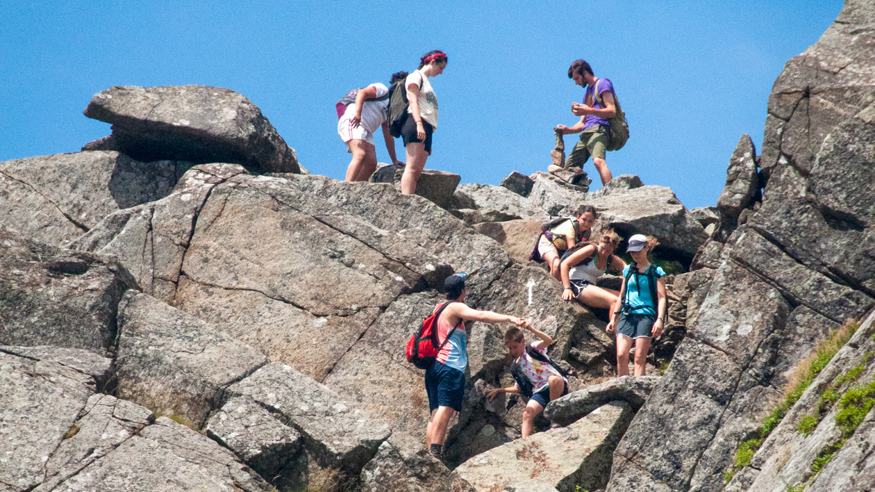 Campers climbing down rocks in the mountains.